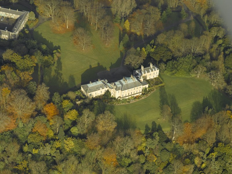 Oblique aerial view centred on the house with the stable block adjacent, taken from the S.