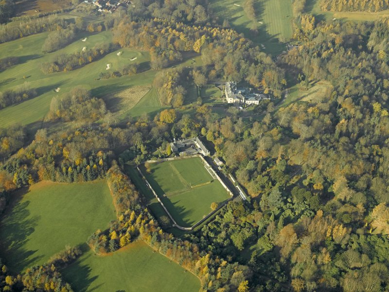 Oblique aerial view centred on the walled garden and stables with the house adjacent, taken from the SE.