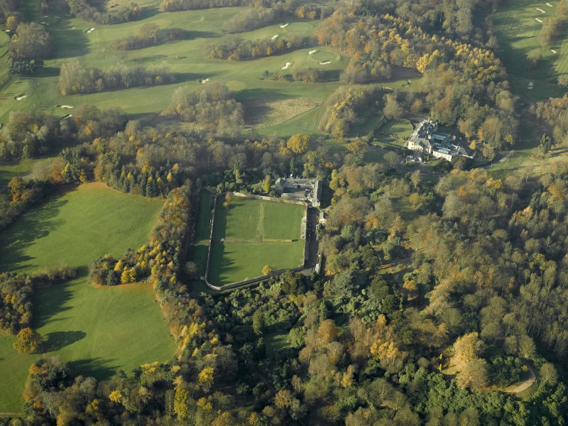 Oblique aerial view centred on the walled garden and stables with the house adjacent, taken from the ESE.