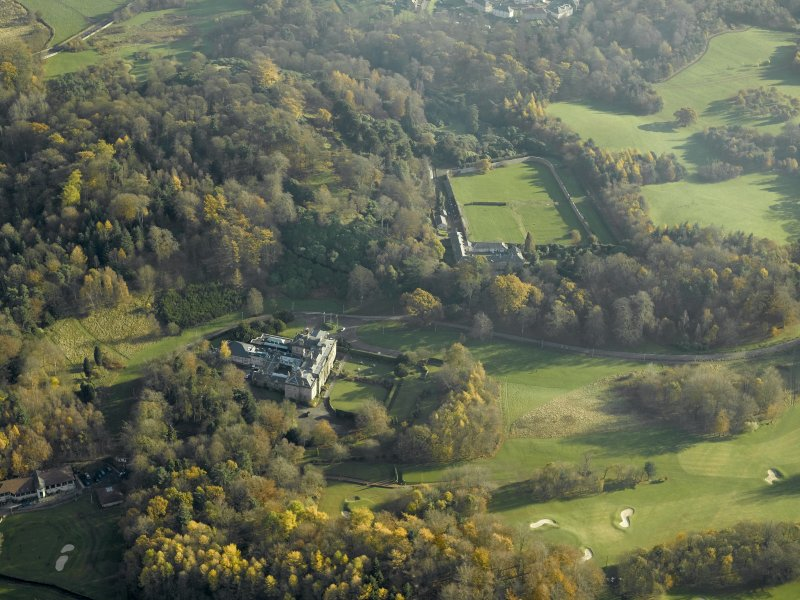 Oblique aerial view centred on the house with the walled garden and stables adjacent, taken from the NW.