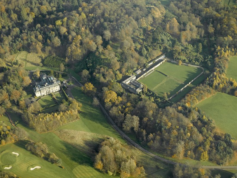 Oblique aerial view centred on the house with the walled garden and stables adjacent, taken from the W.