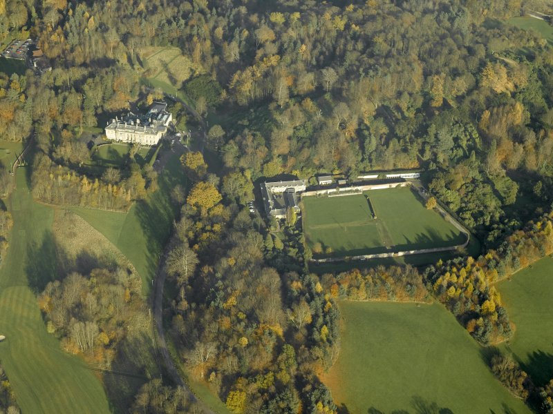 Oblique aerial view centred on the house, walled garden and stables, taken from the SE.