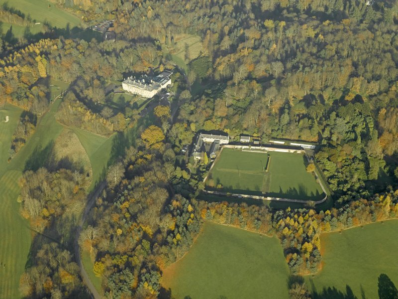 Oblique aerial view centred on the house, walled garden and stables, taken from the SSW.