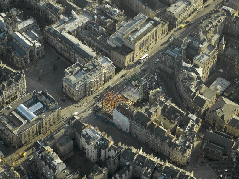 Oblique aerial view centred on new construction work at the junction of High Street and George IV Bridge, taken from the NW.