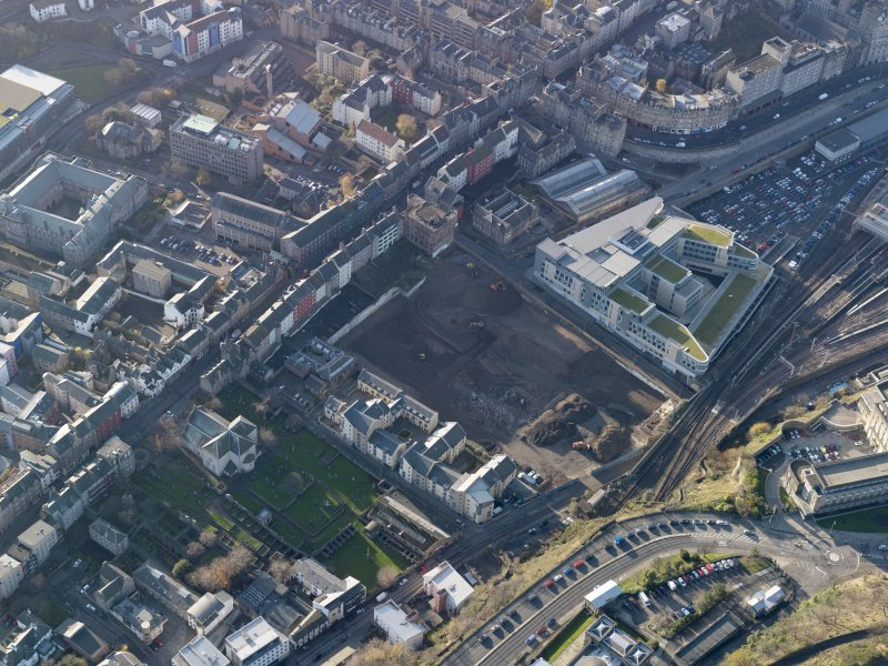 Oblique aerial view centred on the cleared Caltongate development site (former SMT bus garage) with Canongate adjacent, taken from the NE.
