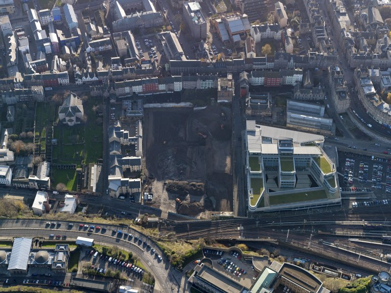Oblique aerial view centred on the cleared Caltongate development site (former SMT bus garage) with Canongate adjacent, taken from the NNW.