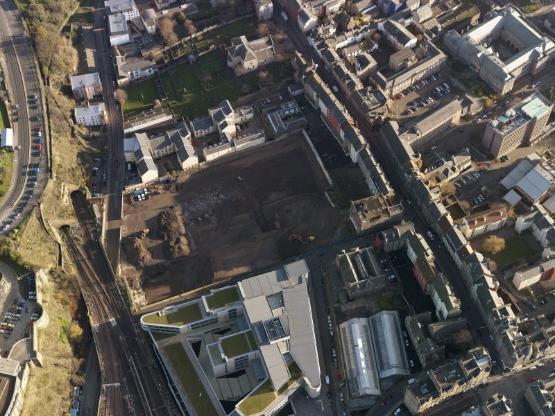 Oblique aerial view centred on the cleared Caltongate development site (former SMT bus garage) with Canongate adjacent, taken from the W.