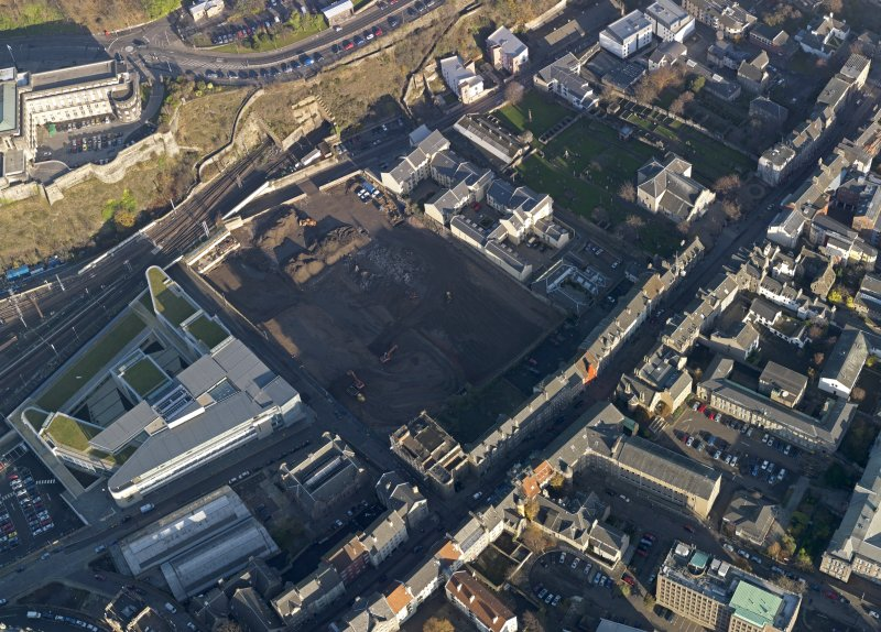 Oblique aerial view centred on the cleared Caltongate development site (former SMT bus garage) with Canongate adjacent, taken from the SW.