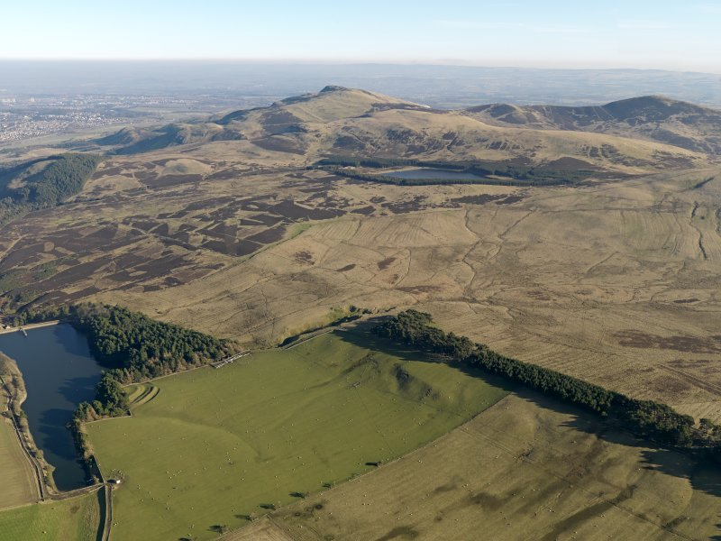 General oblique aerial view centred on the remains of rig and furrow cultivation on the the NW-facing slopes of the Pentland Hills with the remains of a fort adjacent, taken from the WNW.