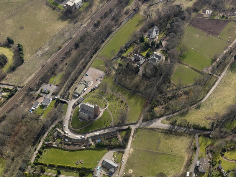 Oblique aerial view centred on the church and manse, taken from the NNW.