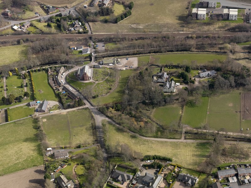Oblique aerial view of St Vigeans centred on the church and manse, taken from the WSW.