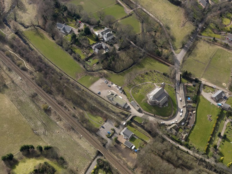 Oblique aerial view centred on the church and manse, taken from the NE.