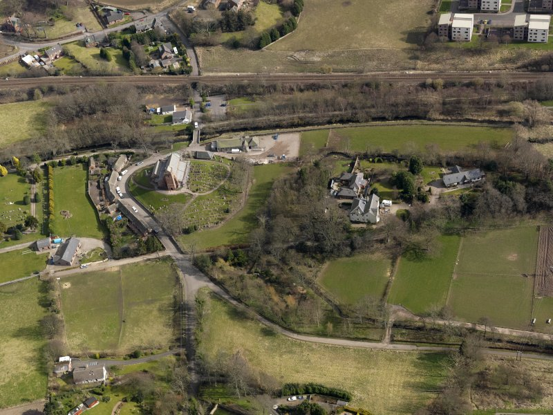 Oblique aerial view centred on the church and manse, taken from the SW.