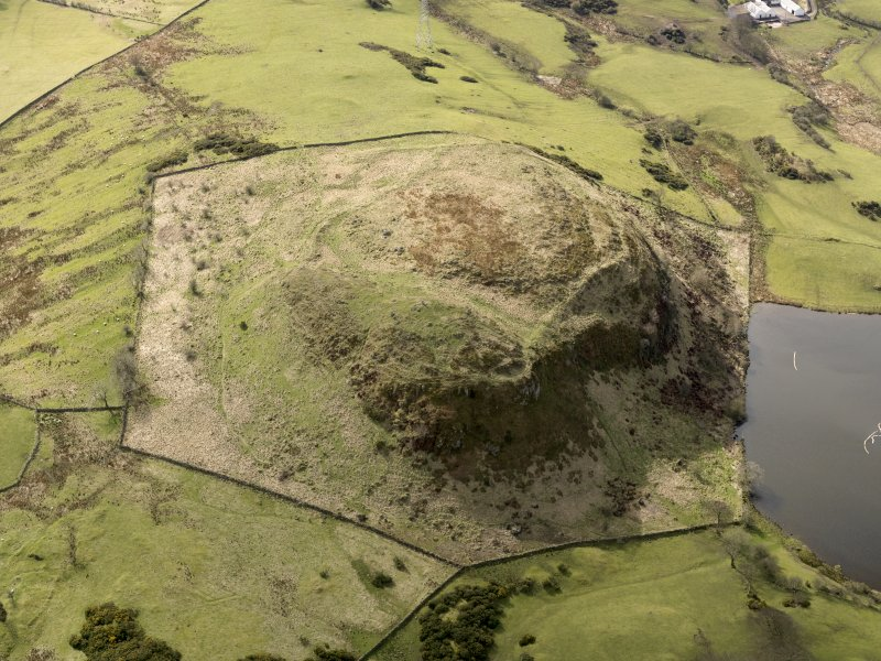 Oblique aerial view centred on the remains of a fort, taken from the NE.