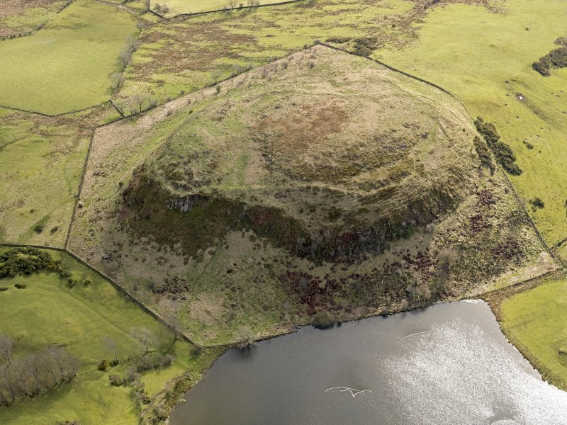 Oblique aerial view centred on the remains of a fort, taken from the NW.