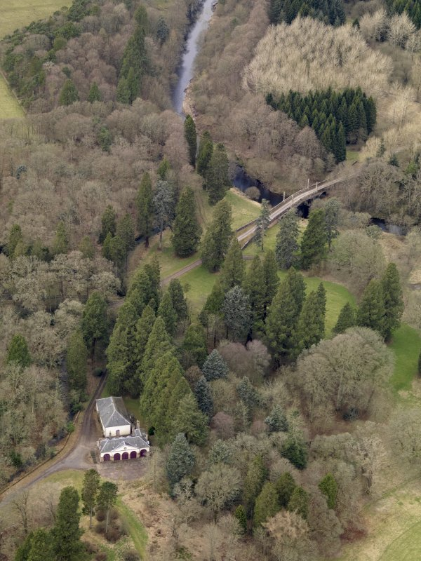 Oblique aerial view centred on the coach house and stables with the Avenue Bridge adjacent, taken from the SE.
