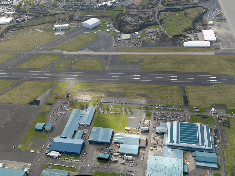 Oblique aerial view centred on the airport with the aircraft factory adjacent, taken from the N.