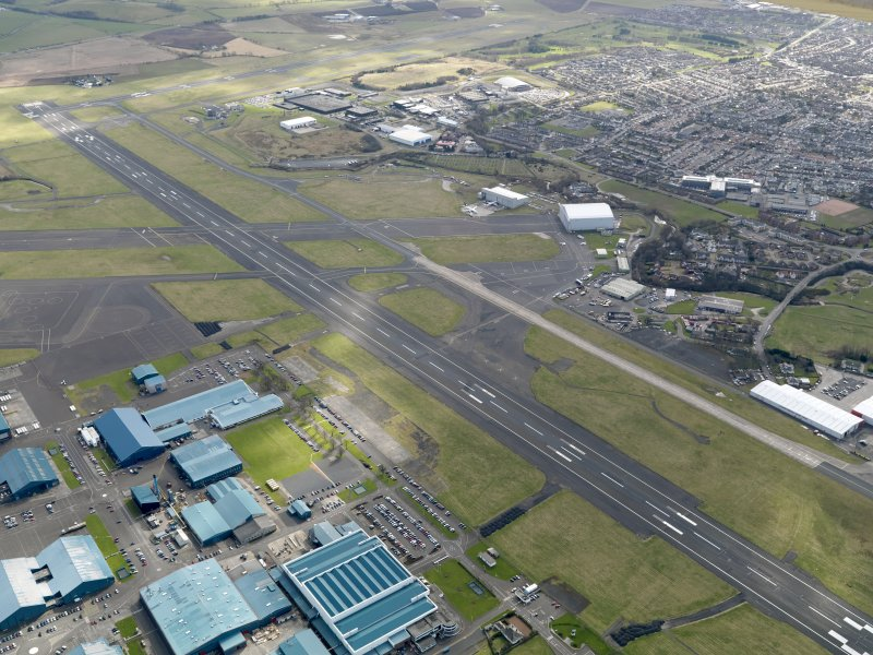 Oblique aerial view centred on the airport with the aircraft factory adjacent, taken from the NNW.