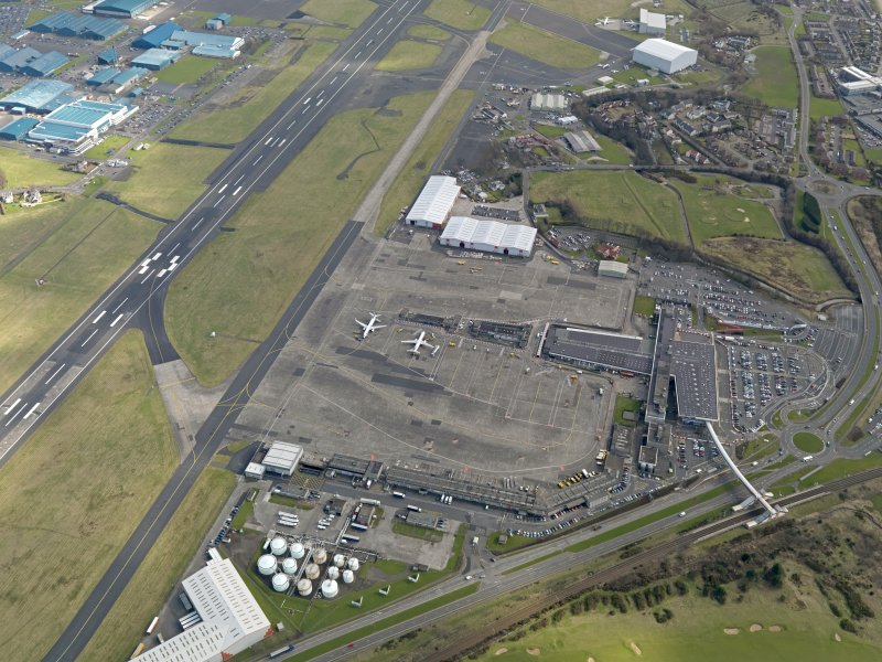 Oblique aerial view centred on the airport terminal buildings with the railway station adjacent, taken from the NW.
