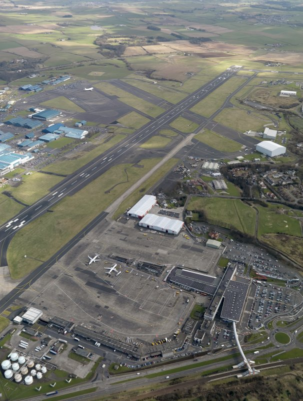 Oblique aerial view centred on the airport terminal buildings, taken from the NW.