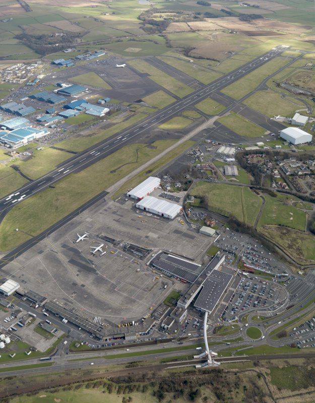 Oblique aerial view centred on the airport terminal buildings, taken from the WNW.