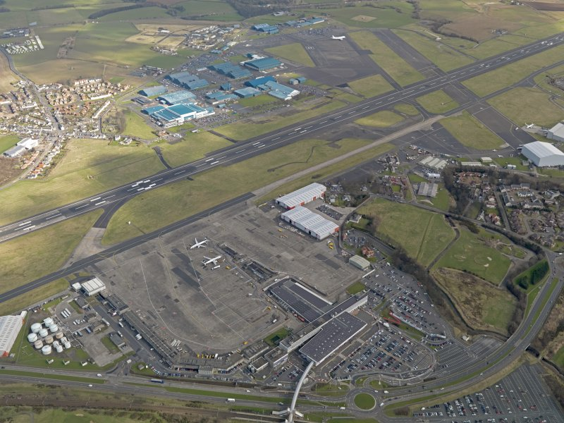 Oblique aerial view centred on the airport terminal buildings, taken from the W.