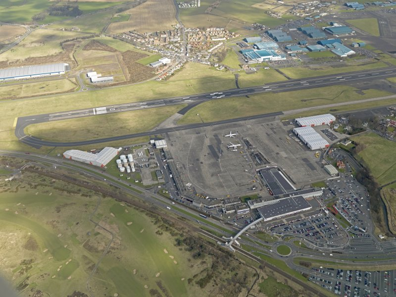 Oblique aerial view centred on the airport terminal buildings with the railway station adjacent , taken from the WSW.