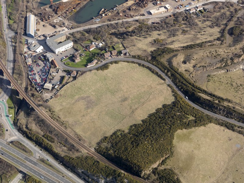 Oblique aerial view centered on the former golf course with the railway viaduct and building adjacent, taken from the SW.