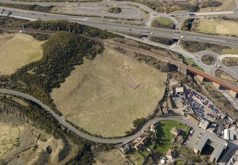 Oblique aerial view centered on the former golf course with the railway viaduct and building adjacent, taken from the NE.
