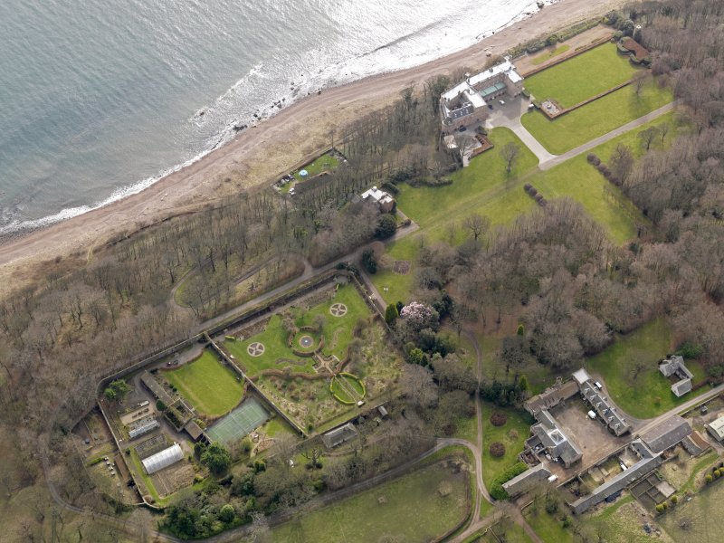 Oblique aerial view centred on the walled garden and orangery with the home farm, houses and tower-house adjacent, taken from the NNW.