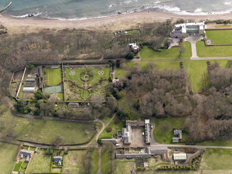 Oblique aerial view centred on the walled garden and orangery with the home farm, cottages, houses and tower-house adjacent, taken from the NW.