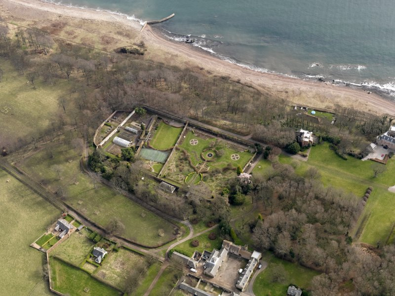 Oblique aerial view centred on the walled garden and orangery with the home farm, house and cottages adjacent, taken from the WNW.