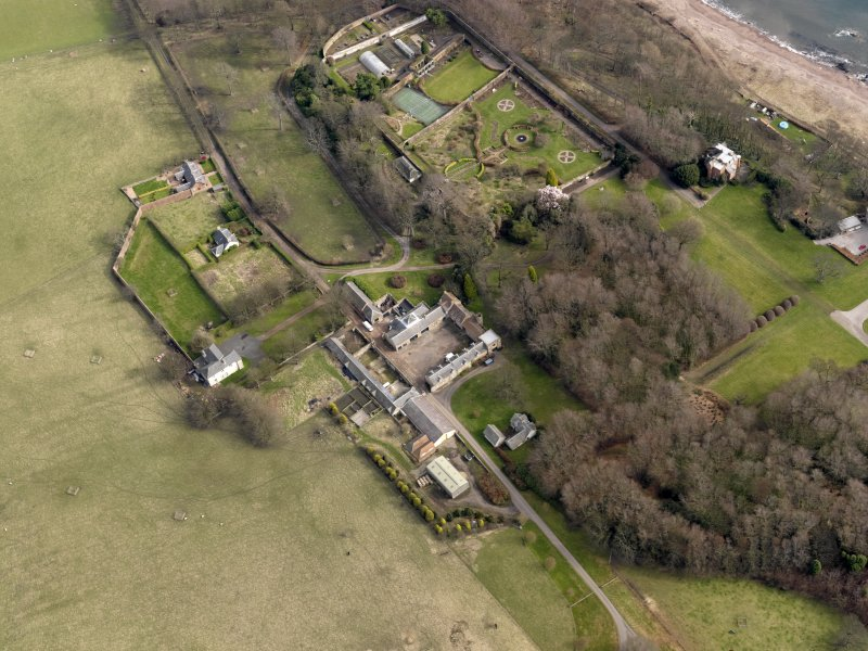 Oblique aerial view centred on the home farm with the cottages, houses and walled garden and orangery adjacent, taken from the W.
