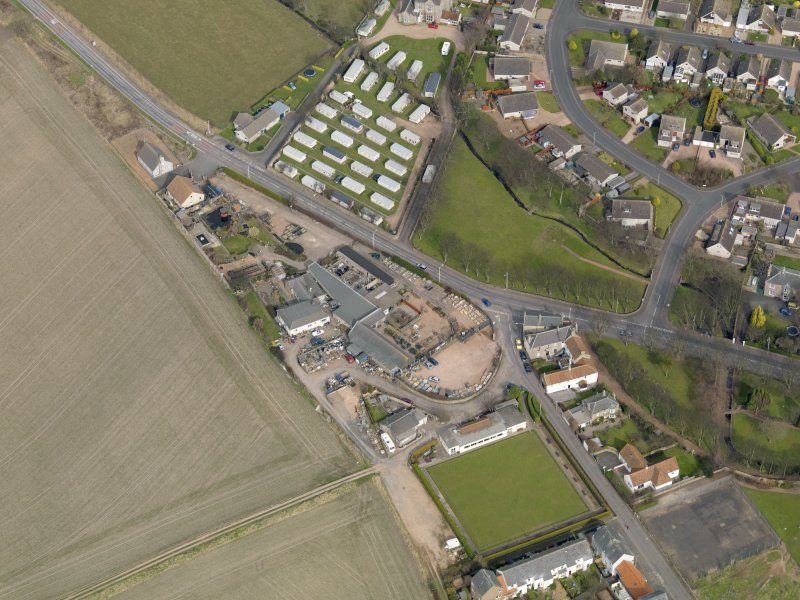Oblique aerial view centred on the garden centre with the bowling green adjacent, taken from the S.