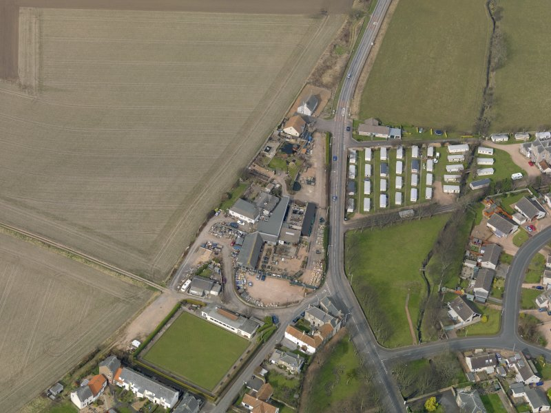 Oblique aerial view centred on the garden centre with the bowling green adjacent, taken from the SSE.