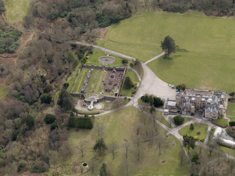 Oblique aerial view centred on the house with the walled garden adjacent, taken from the N.