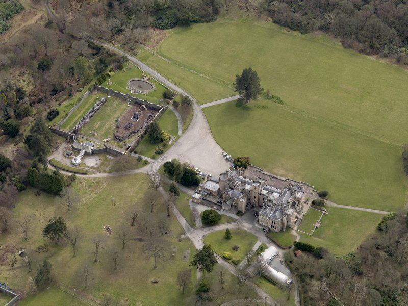 Oblique aerial view centred on the house with the walled garden adjacent, taken from the NW.