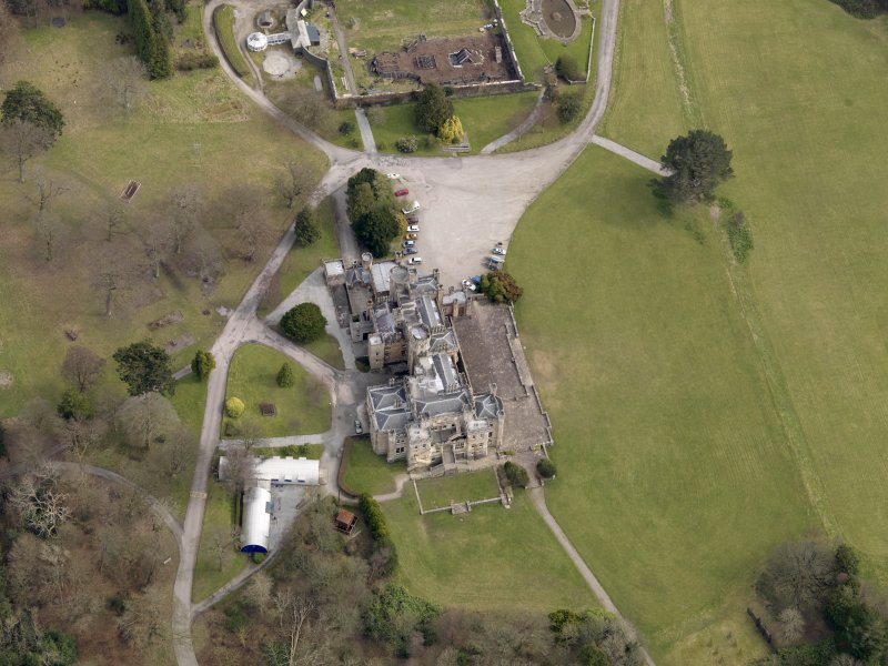 Oblique aerial view centred on the house with the walled garden adjacent, taken from the W.