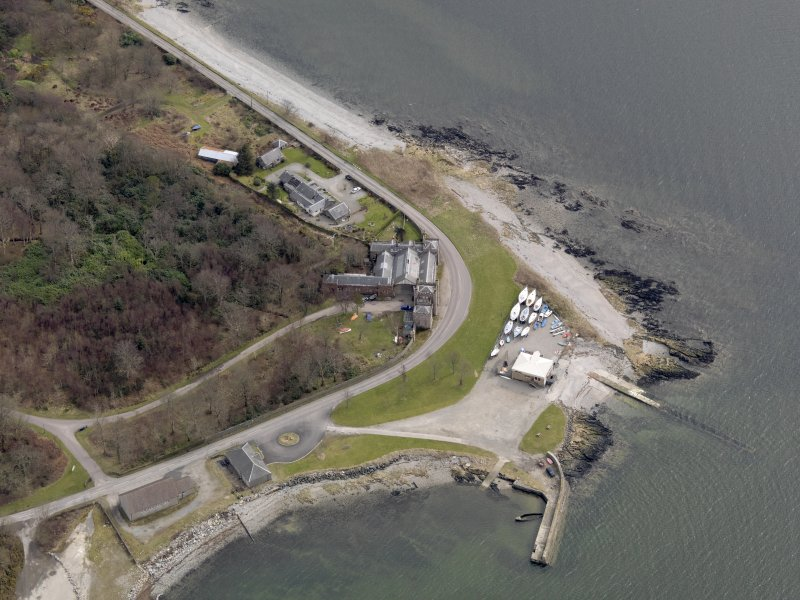 Oblique aerial view centred on the South Lodge, with the pier and quay adjacent, taken from the NW.