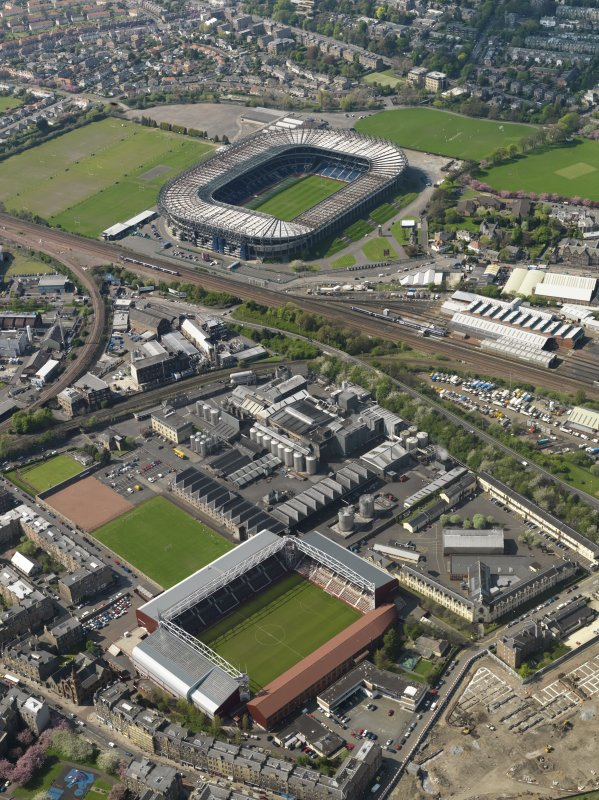 Oblique aerial view of Edinburgh centred on the Tynecastle Park football stadium with the North British Distillery adjacent and Murrayfield Stadium in the background, taken from the SE.