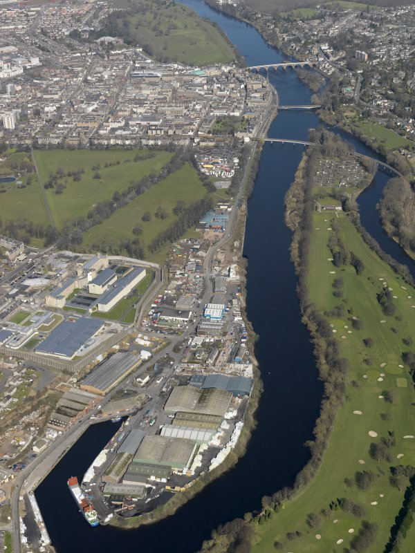 General oblique aerial view looking along the River Tay with the harbour and prison in the foreground and the bridges in the distance, taken from the S.