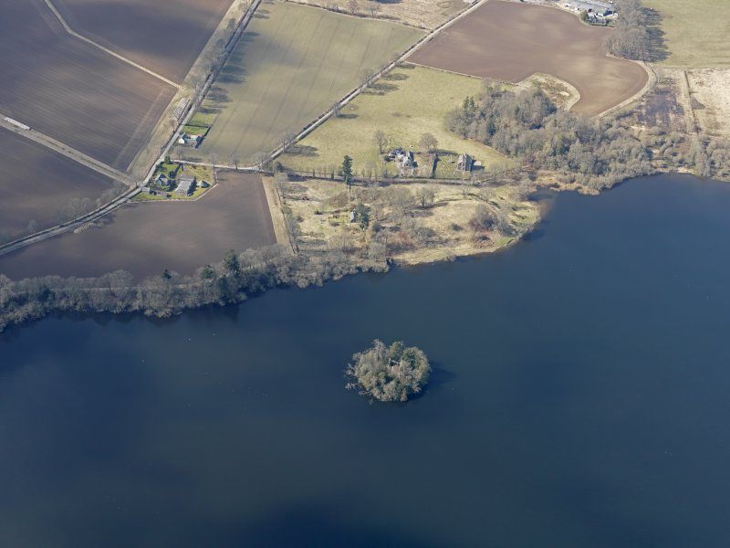 General oblique aerial view of the church and the remains of the earthwork castle, with the chapel and towerhouse on the island, taken from the E.