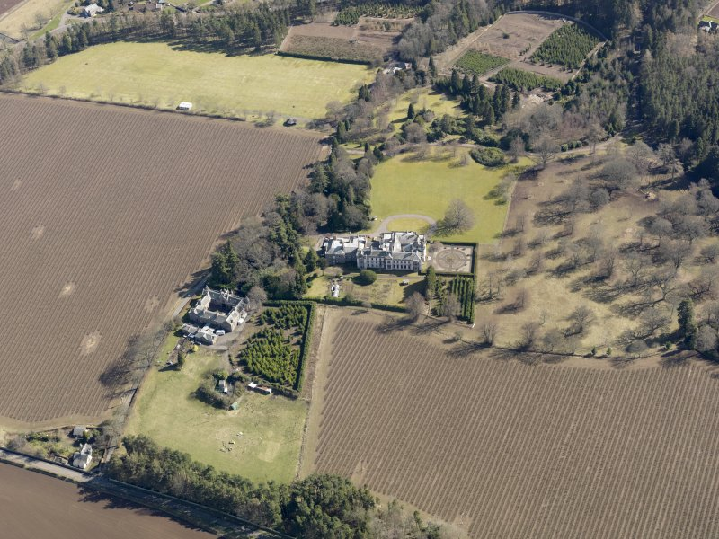 Oblique aerial view centred on the country house and stables, taken from the NW.