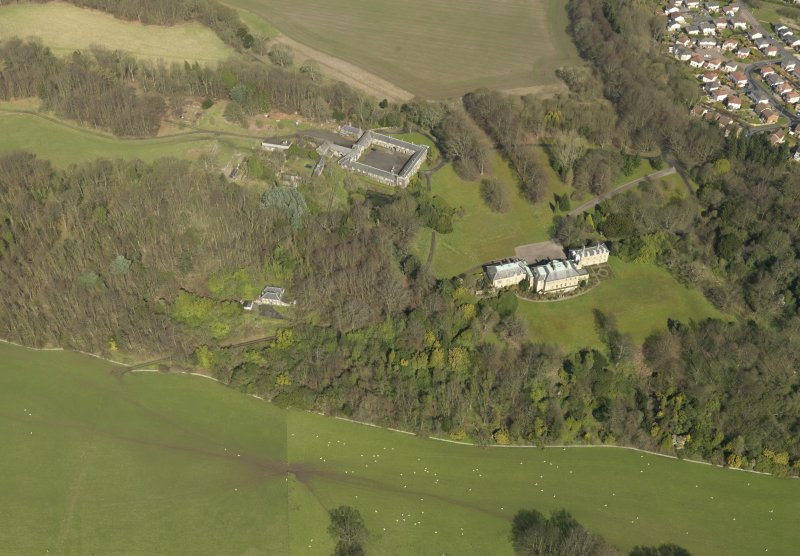 General oblique aerial view centred on the house with the stable block adjacent, taken from the S.