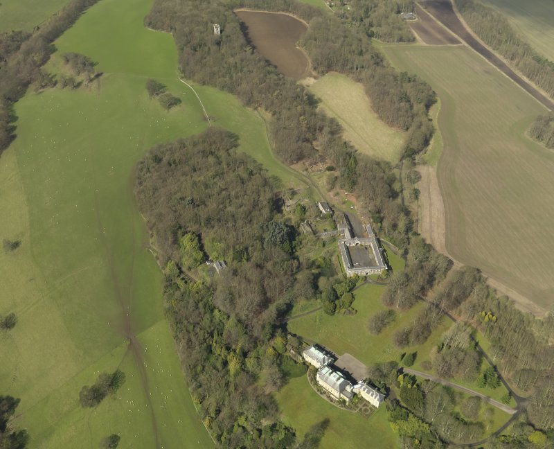General oblique aerial view centred on the house with the stable block adjacent, taken from the SE.