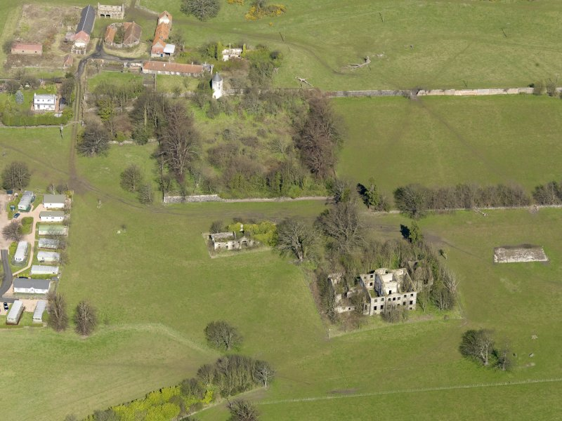 Oblique aerial view centred on the remains of the house with the remains of the stables adjacent, taken from the S.