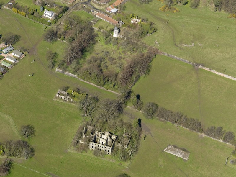 Oblique aerial view centred on the remains of the house with the remains of the stables adjacent, taken from the SSE.