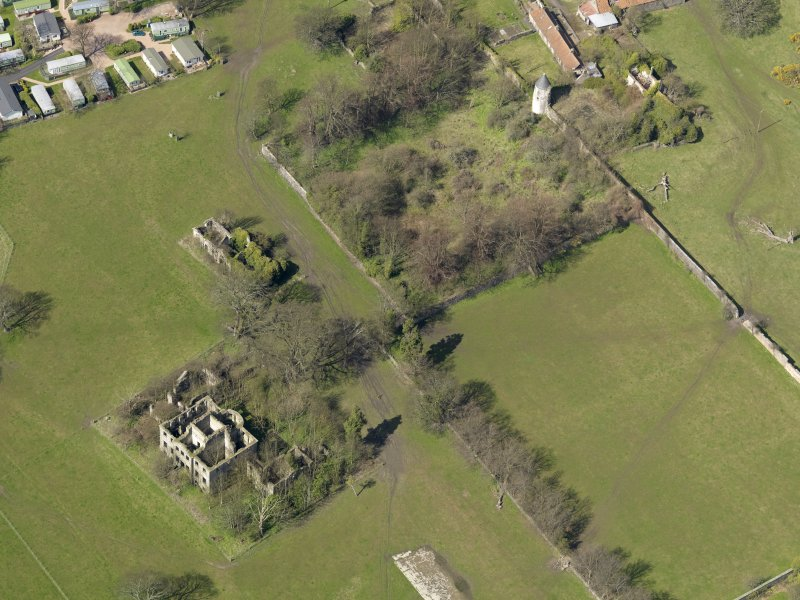 Oblique aerial view centred on the remains of the house with the remains of the stables adjacent, taken from the SE.