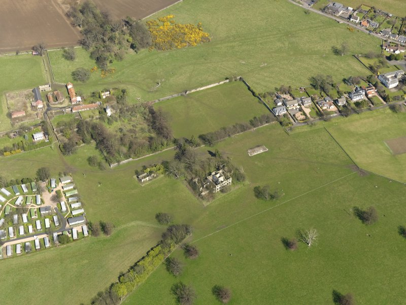 General oblique aerial view centred on the remains of the house with the remains of the stables adjacent, taken from the SW.
