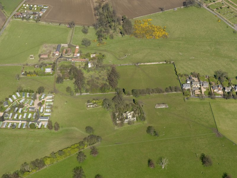 General oblique aerial view centred on the remains of the house with the remains of the stables adjacent, taken from the S.